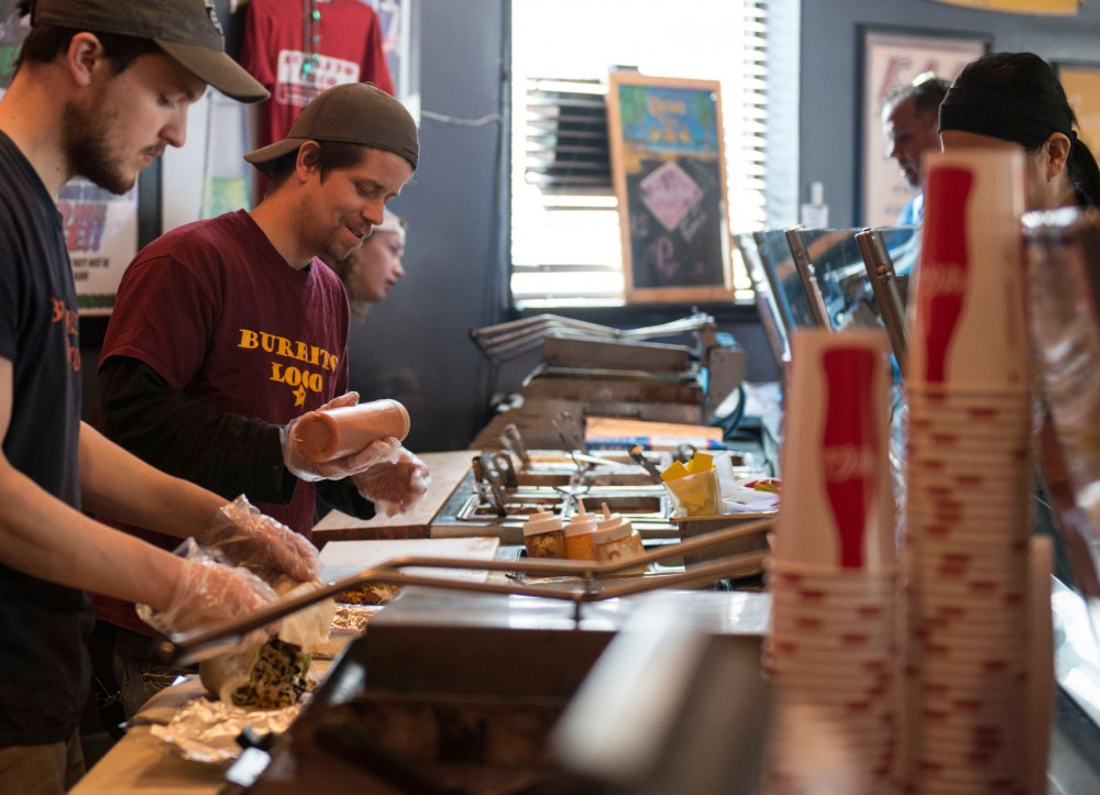 Burrito Loco employee John Cousins prepares food for a customer. Burrito Loco is a local business that pays some employees minimum wage, and could be affected by the new Minnesota mimim wage increase.