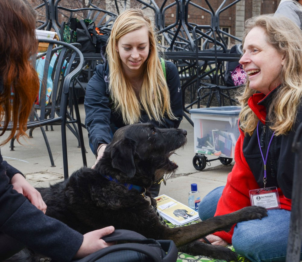 PAWS volunteer Cheryl Gfrerer and her dog named Sarah spend time greeting students to assist with stress management for Mental Health Awareness Day on Wednesday, April 23.
