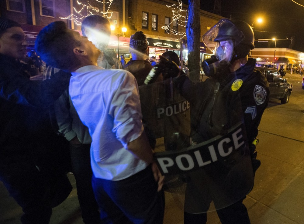 Minneapolis police officer sprays tear gas at a man in front of Espresso Royale on Thursday evening. People stormed Dinkytown following the Gophers men's hockey semifinal win against North Dakota.