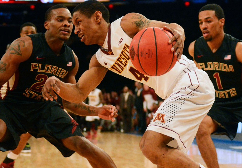 Minnesota guard DeAndre Mathieu drives past two Florida State defenders Tuesday night at Madison Square Garden in New York.