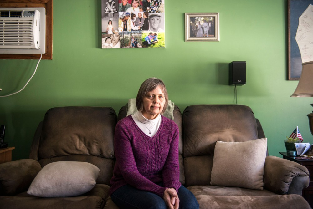 Mariana Shuck sits in the livingroom of her Burnsville home, March 8. A collage of their family made my Anarae hangs above her head along with other family photos.