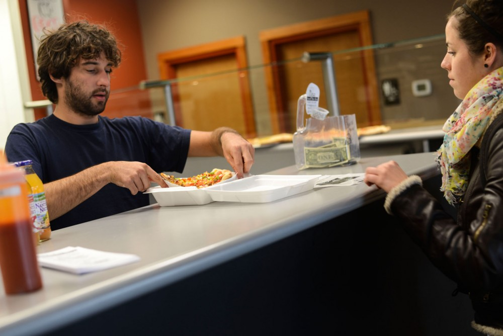 General Manager Wade Kapphahn serves a piece of pizza in a styrofoam box to graduate student Erica Bye at Mesa Pizza in Stadium Village on Wednesday.