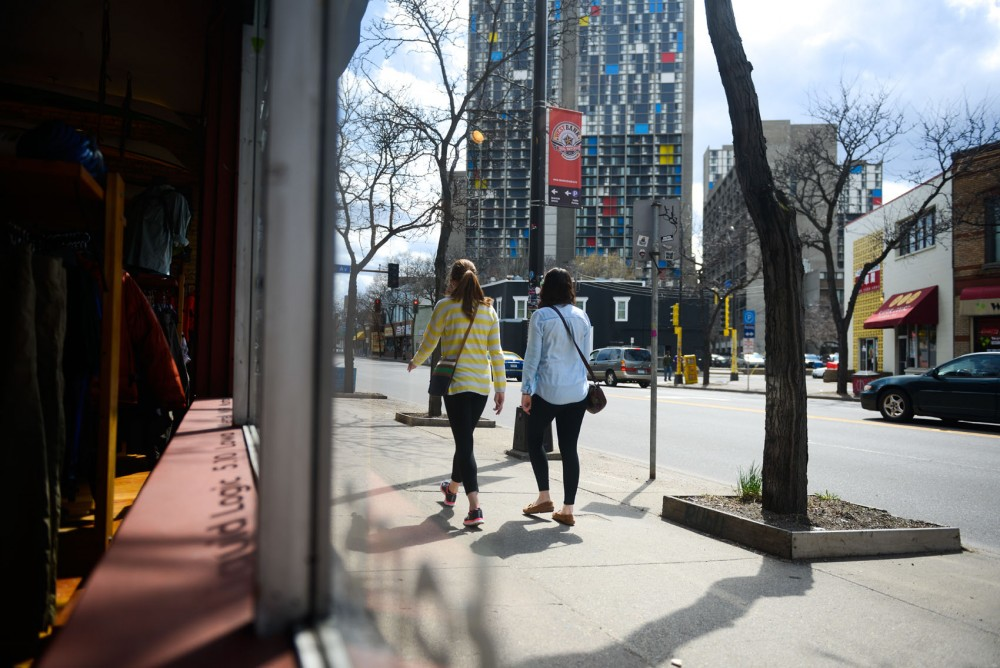 Two girls walk on the sidewalk outside of Midwest Mountaineering on Cedar Avenue on Saturday.  The sidewalks and Cedar Avenue between 3rd and 7th Street are going to be renovated this summer.
