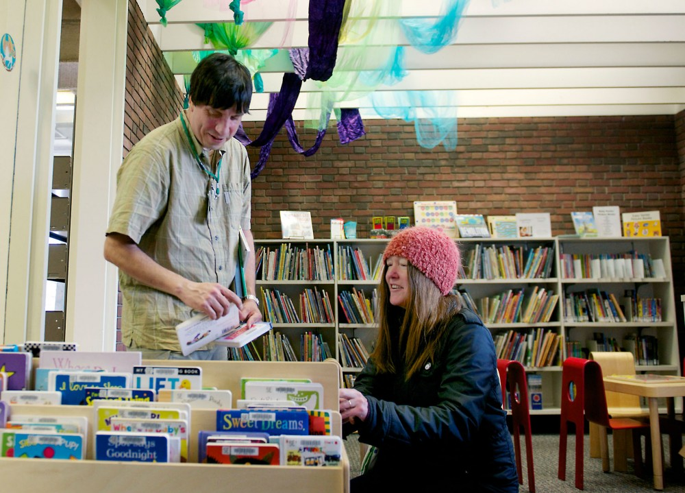 Emily Ruiz sorts books with office specialist James Ruiz at the Hennepin County Southeast Library on Tuesday.