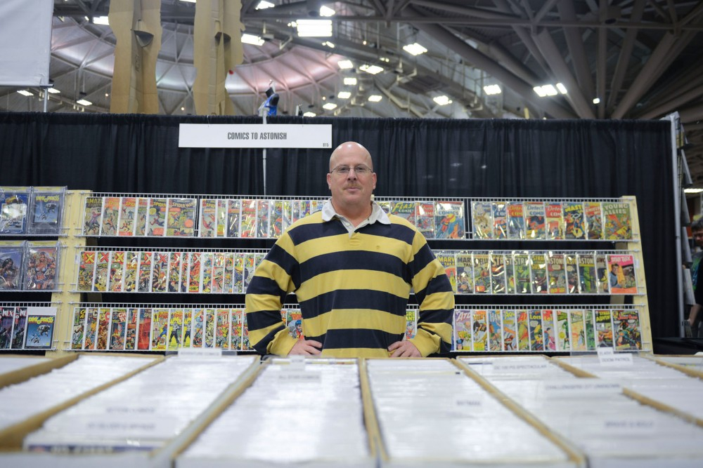Comics to Astonish owner Keegan Conrad stands in front of his collection of comic books for sale at the Convention Center on Saturday. This weekend, Wizard World held its first Minneapolis Comic Con.