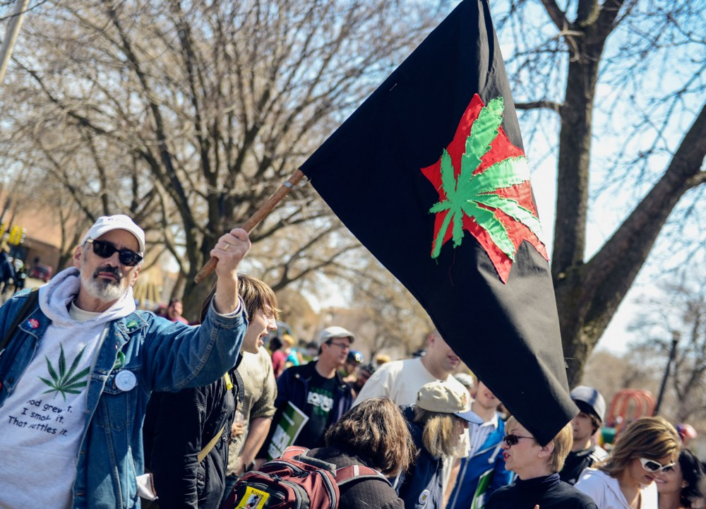 Marion Delgado, supporter of the National Organization for the Reform of Marijuana Laws, waves a flag displaying a marijuana leaf in in preparation to march in the 40th Annual MayDay Parade in Minneapolis on Sunday.
