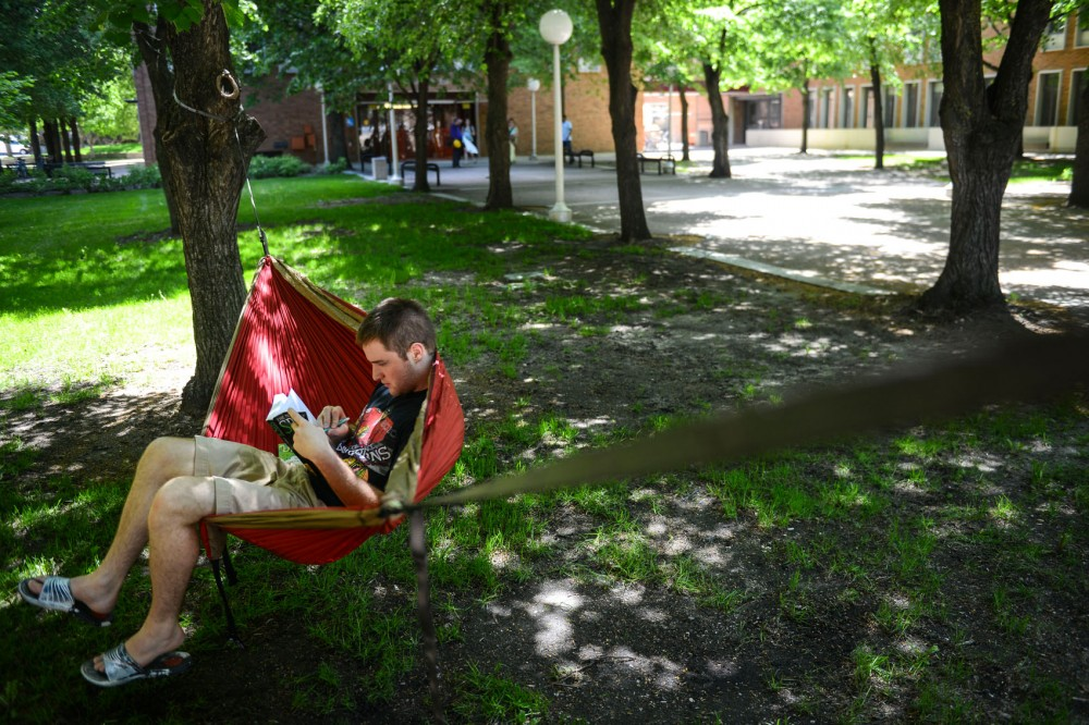 Second-year geography graduate student Joe Witek reads in a hammock on West Bank on May 29.
