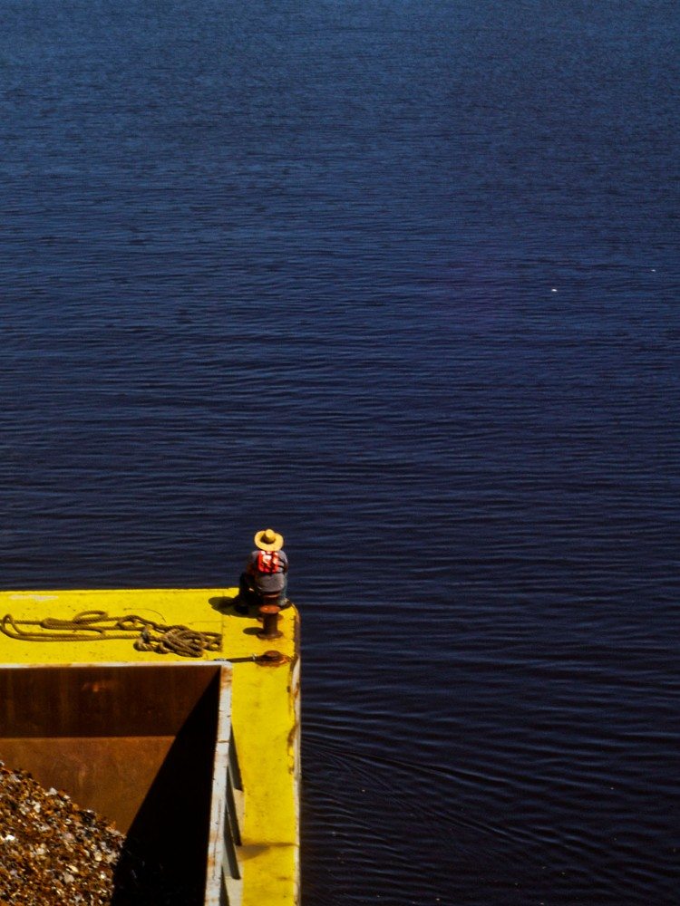 A man sits on the end of a barge going down the Mississippi river near the Stone Arch Bridge on Thursday, May 29