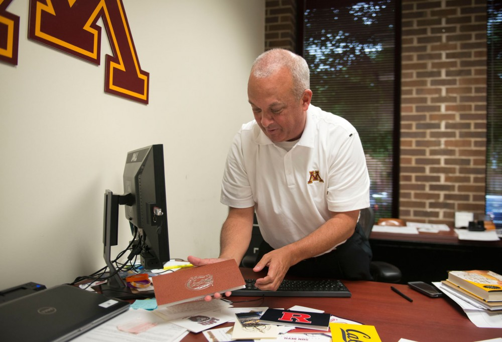 Gophers executive associate athletics director Mike Ellis shows his thank-you cards in his office at Bierman Field Athletic Building on Thursday. Ellis is one of the founding members of Villa 7, a networking event to introduce assistant coaches to potential employers.
