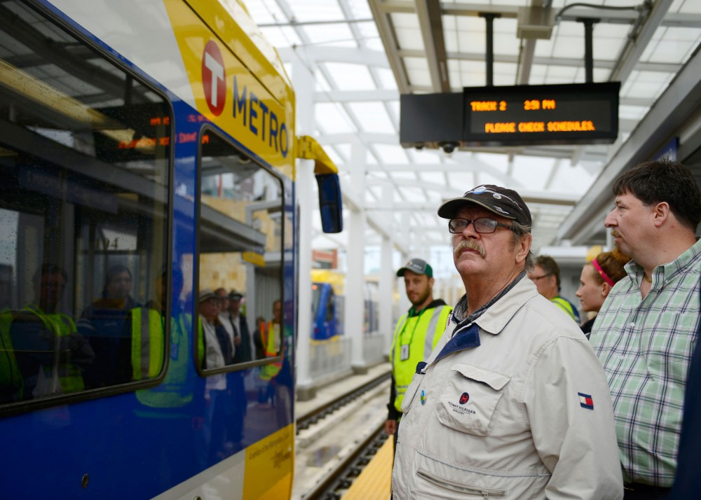 A passenger waits to board the Green Line at Target Field Station on Saturday. Despite the rain, the opening day of the Green Line drew large crowds to ride the new light rail between Minneapolis and St. Paul.