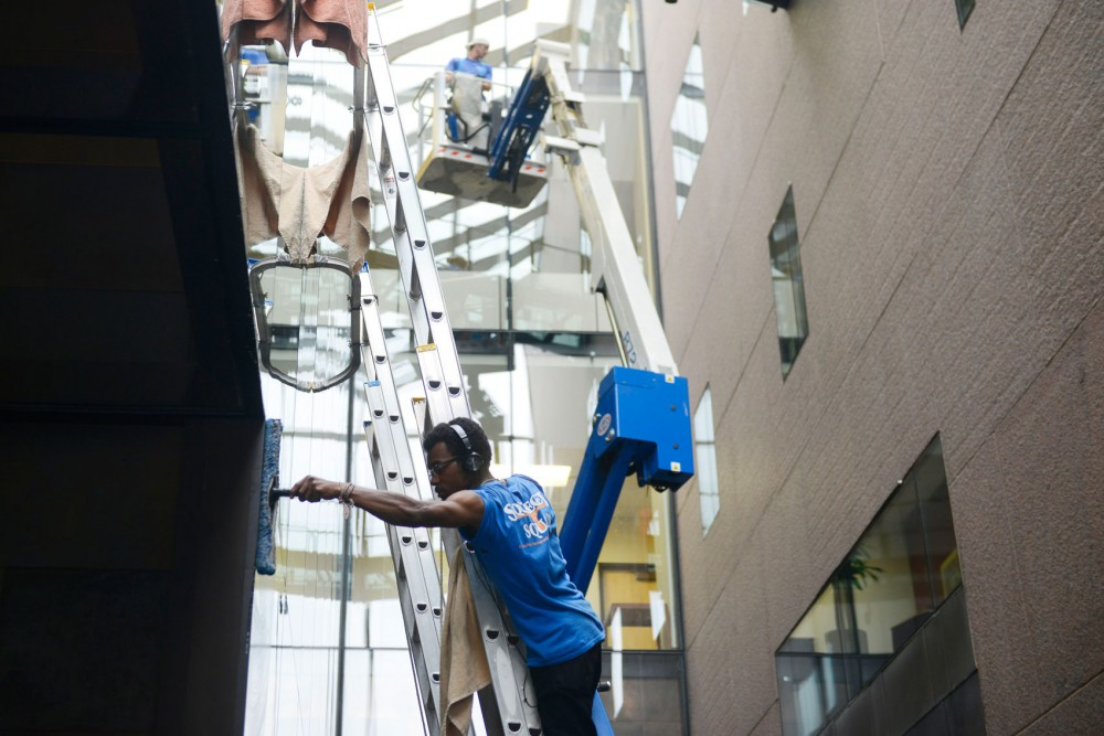 The windows at McNamara Alumni Center get a thorough window cleaning by Squeegee Squad cleaners on Monday afternoon.