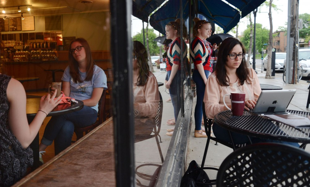 People sit inside and outside of Espresso Royale on Monday.