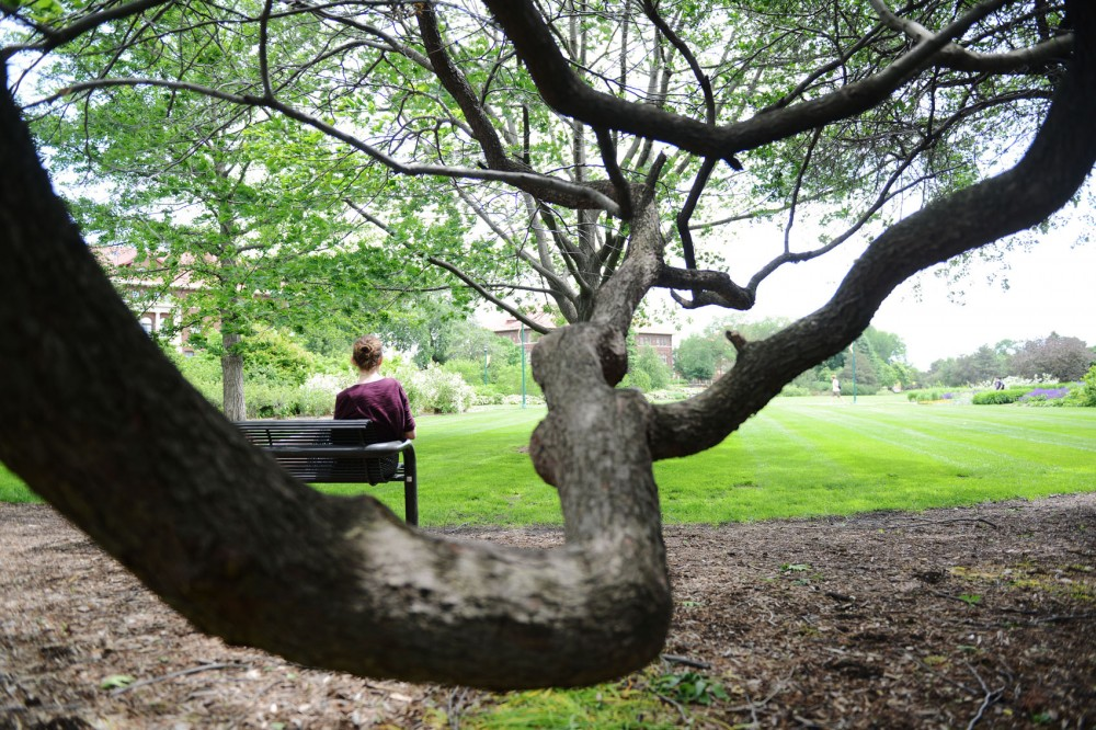 Katie Gallagher, designer at the University of Minnesota Extension, sits on a bench in the sun on the St. Paul campus on Monday.