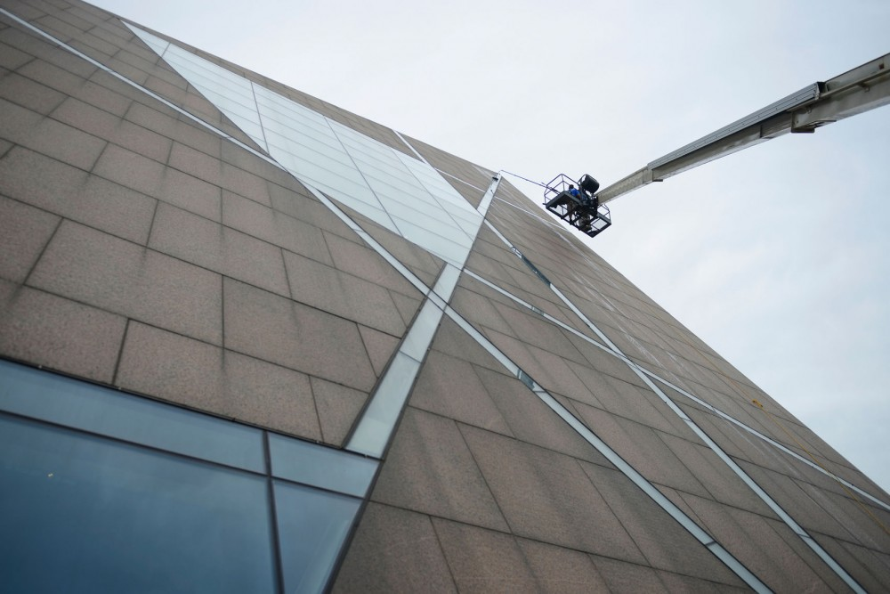 The windows at the McNamara Alumni Center get cleaned by Squeegee Squad cleaners on Monday afternoon.