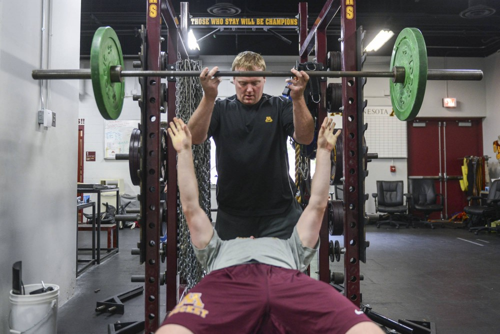 Strength and conditioning coach Cal Dietz spots Gophers men's hockey player Sam Warning as he lifts weights in the Mariucci Arena weight room Thursday.