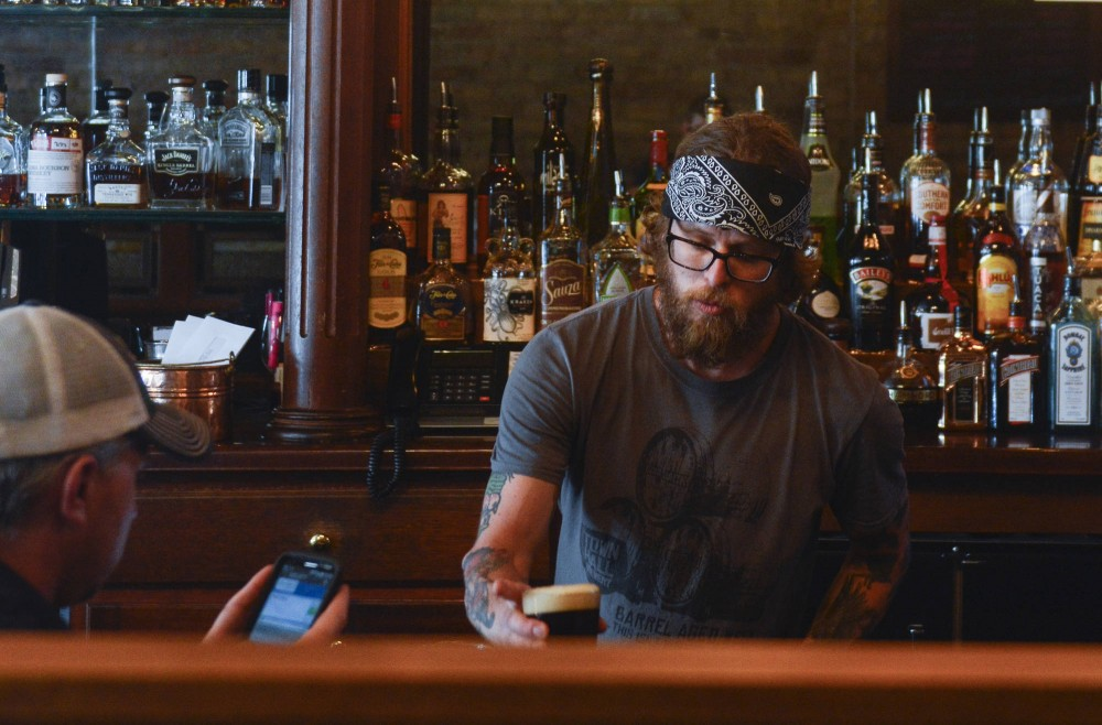 Patrick Moen gives a drink to a customer at Minneapolis Town Hall Brewery on Monday. Moen is one of many servers whose wages could be capped at $8 an hour if advocates continue pushing for a tipped employee tier next session.