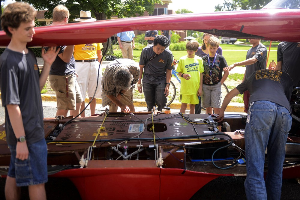Team members of the University of Minnesota Solar Vehicle Project raise the shell of the completed solar car on the St. Paul campus on Tuesday, to reveal its interior for bystanders. The UMNSVP will race its solar car in an international race starting next Monday.