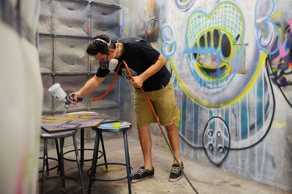 Second year painting graduate student Mark Schoening spray paints a clear coat on one of his paintings in the spray booth at the Regis Center for Art on Monday morning.