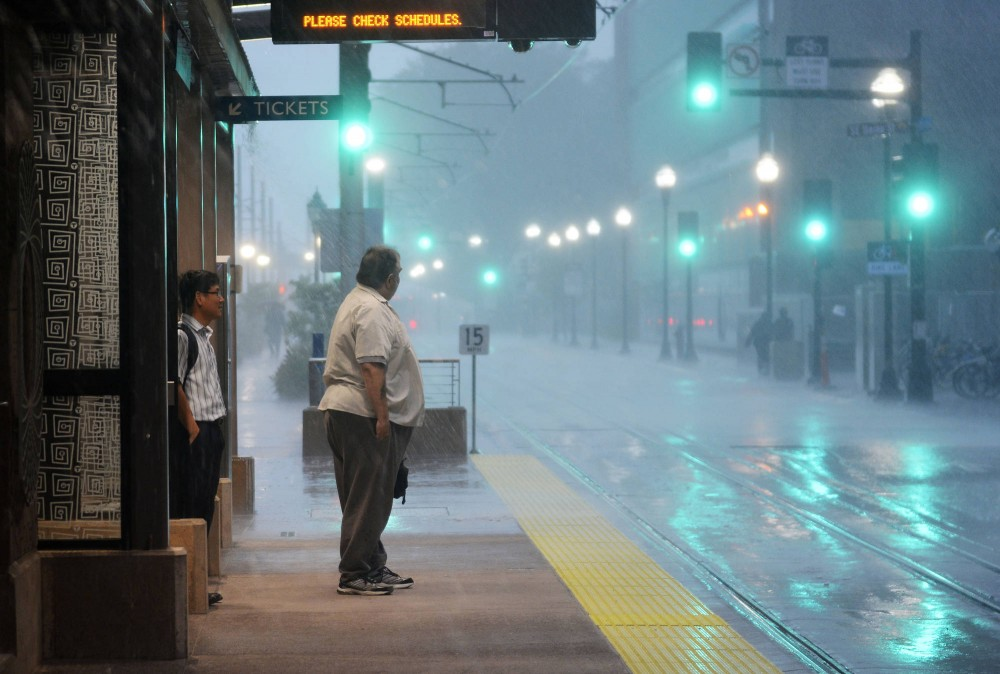 Two men wait at the Light Rail station during while it rains Monday evening.