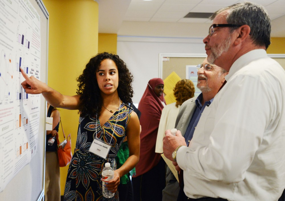Biology, society and environment senior Ambrosia Smith talks to President Eric Kaler about her research on females and drug addiction at the McNair Scholars Poster Presentation in Coffman on Thursday.