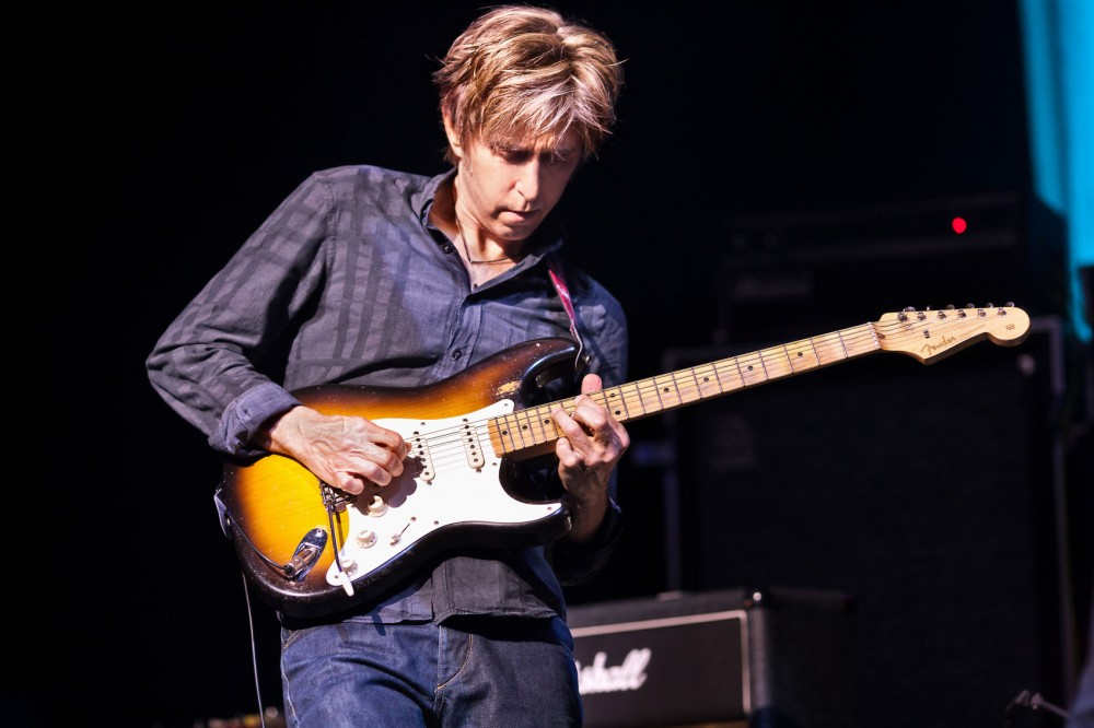 Eric Johnson plays emotional, scale sweeping solos on electric guitar.