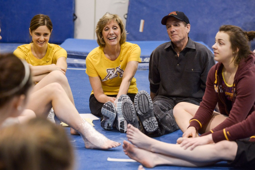 Women's gymnastics head coach Meg Stephenson, left, and assistant coach Jim Stephenson speak with their team after they finished competing in an in-house meet on /date/ at Peik Gymnasium. This season the Gophers qualified for the NCAA Championships for the first time since 2002.