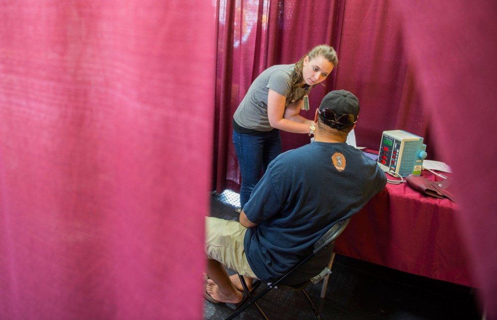 Fourth year medical student Mariel Lougee works with research participant Milton Dodd at the Driven to Discover Research Building on Sunday afternoon at the Minnesota Sate Fair. People of all ages participated in the more than 30 studies hosted at the site over the fair's 12-day run.