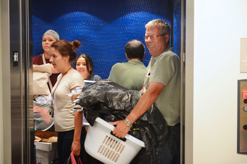 Students and parents bring belongings to their apartments on move-in day at The Venue on Friday, Aug. 29, 2014. The Venue is a new luxury apartment complex on campus.