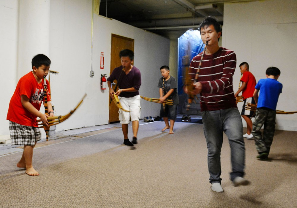 Junior Chai Lee leads a group of students playing flute-like instrument called qeej's in a traditional Hmong art on Monday.