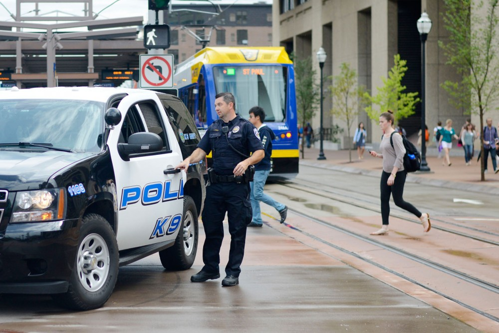 UMPD Officer J. Printz observes pedestrians crossing Washington Avenue, assuring they abide by the walk signals. Following the recent fatality in Prospect Park, the University increases LRT accident prevention with help from Metro Transit Police.