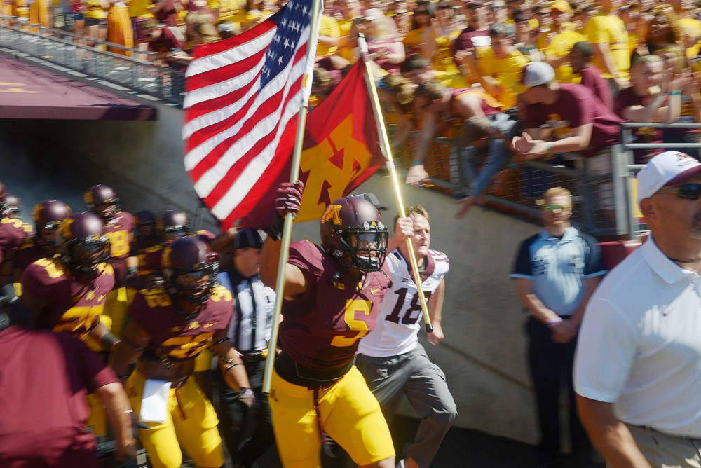 Minnesota linebacker Damien Wilson carries the United States flag onto the field Saturday prior to the game against Middle Tennessee State at TCF Bank Stadium.