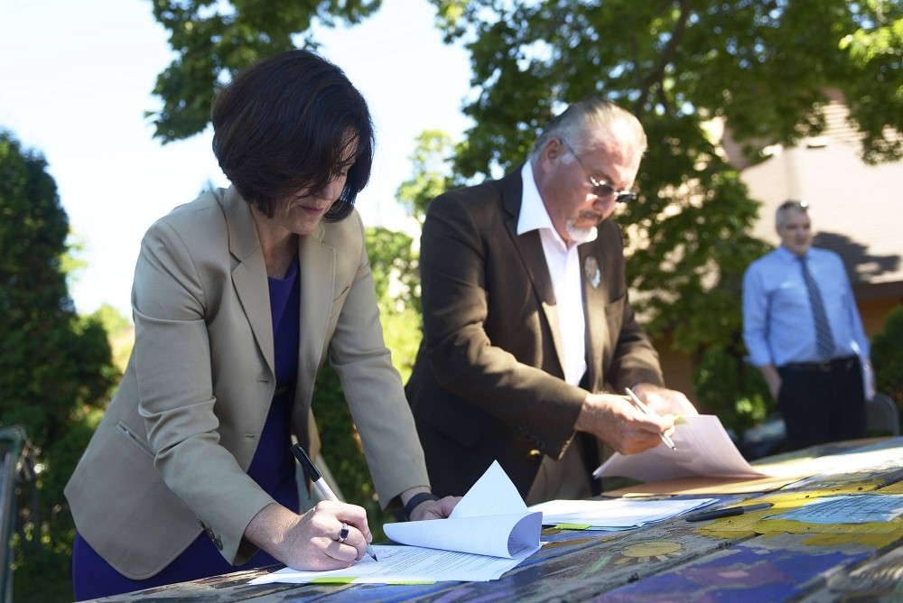 Mayor Betsy Hodges signs an initiative with Chair of the Shakopee Mdewakanton Sioux Community Charlie Vig, at a local urban garden that used biochar to grow its plants on Tuesday in Minneapolis. The University, Minneapolis and Shakopee Mdewakanton Sioux Community are amongst the first in the nation to research biochar in farming.