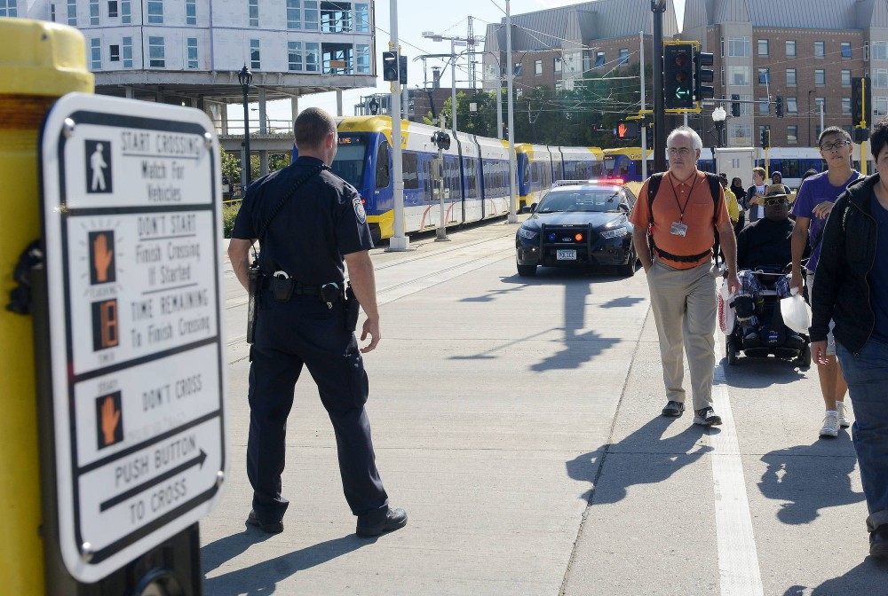 A police officer ushers pedestrians across the street on Monday following a light rail power system issue that affected over seven green line stops. Silmultaneous to the issue was a gas leak in the Wahu apartment complex next to the intersection.