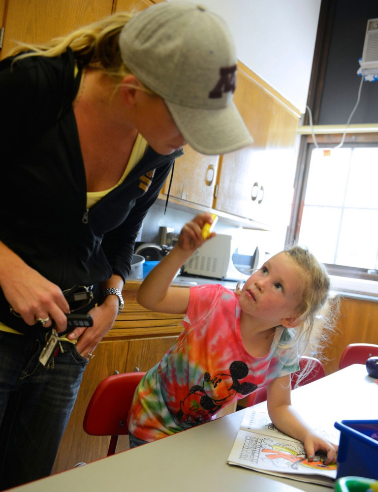 Fire-year-old Harlee Sheid tries to get her mother Stevie, a University student, at the after school program Minneapolis Kids on Monday afternoon in Minneapolis. Minnesota Public Schools are now offering all day kindergarten, which lessens the cost of child care for many parents.