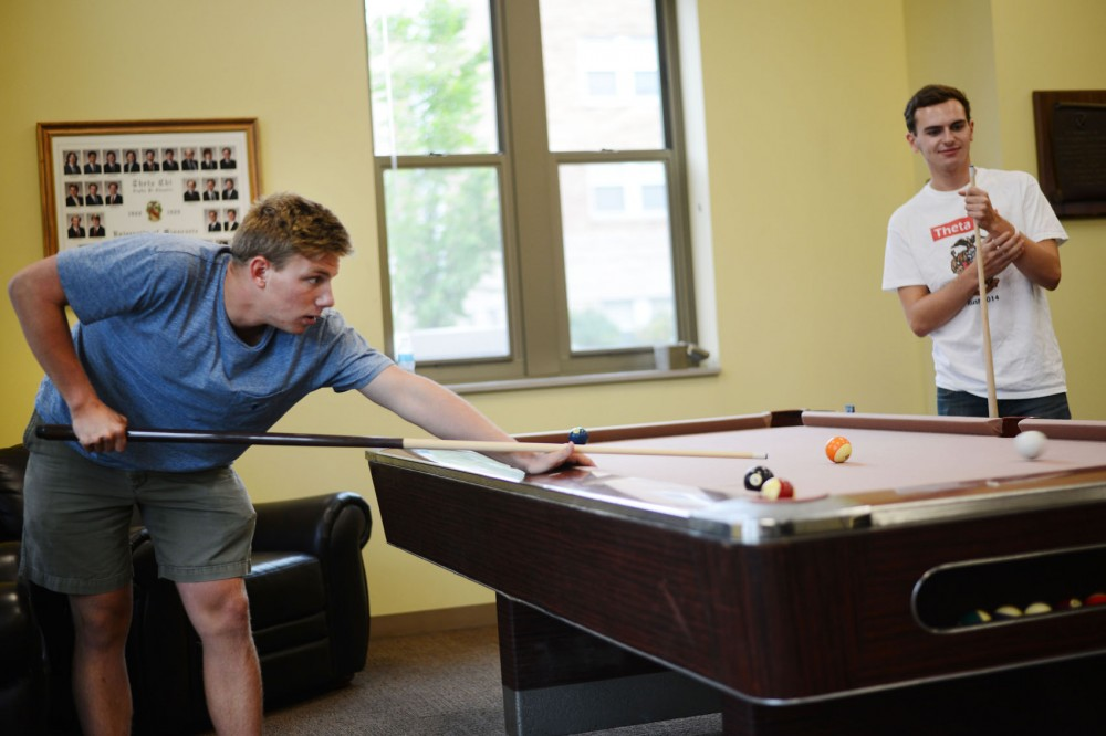 Theta Chi members Blake Kraussel and Andy Buckley play pool in their house on 17th Avenue on Tuesday. Despite experiencing the two Greek organizations experiencing success at this locations, both chapters are planning to move out of 17th Avenue and find permanent housing in larger spaces off campus.