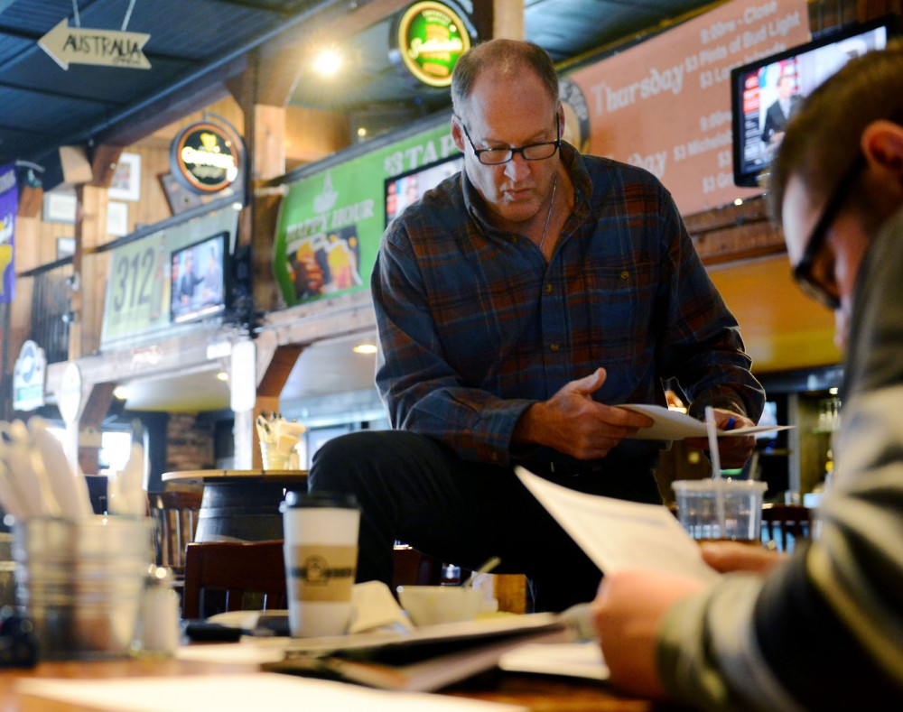Mike Mulrooney, new Dinkytown Business Alliance president, completes paperwork inside Blarney Pub and Grill Tuesday afternoon. He assumed his position in August.