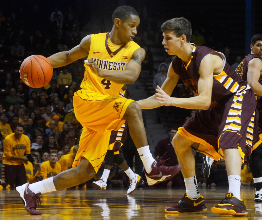 Guard Deandre Mathieu tries to escape a block on Thursday at Williams Arena. The Gophers won the preseason game against the UMD bulldogs 95-68.