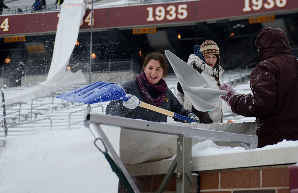 Grad students Cassie Drozynski, left, and Teresa Logemann shovel and remove snow from the stands and onto the field at TCF Bank Stadium on Wednesday afternoon.