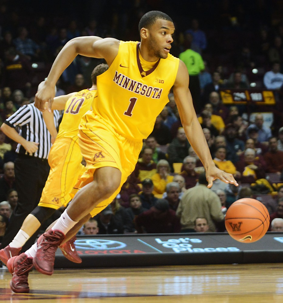 Minnesota guard Andre Hollins pushes the ball up the court against Coastal Carolina on Tuesday, Nov. 19, 2013 at Williams Arena.