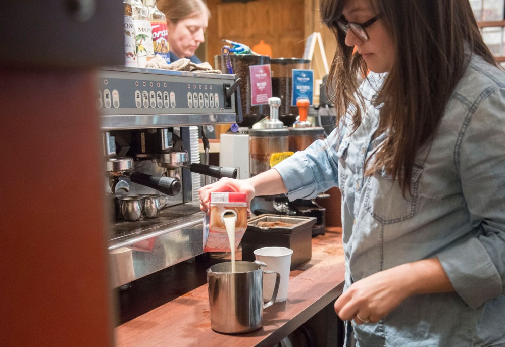 Barista Allison Noble makes a drink with soy milk Monday, Nov. 10 at Bordertown Coffee. Local businesses say they are trying to avoid increasing their prices while the cost of milk rises.