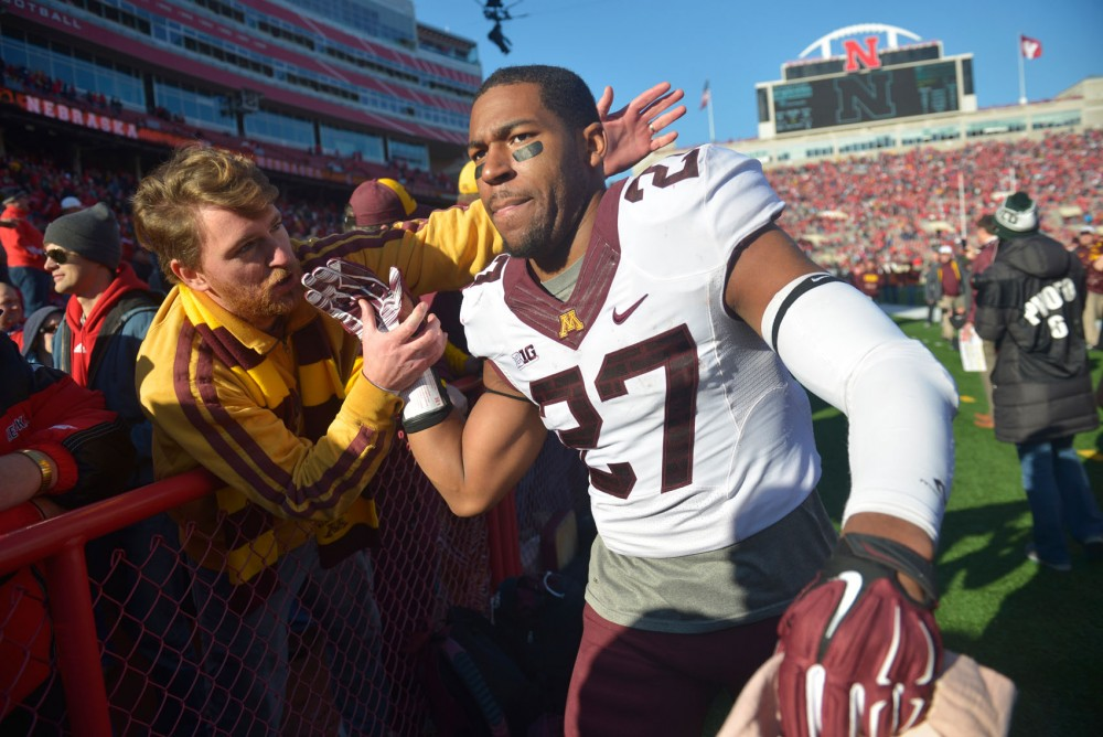 Senior running back David Cobb is congratulated by a fan after the Gophers' victory at Memorial Stadium in Nebraska. Cobb left the game with an injury, and backups Rodrick Williams and Donnell Kirkwood came on to replace him.