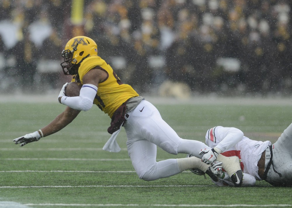 Gophers running back David Cobb gets pulled to the ground on Saturday, Nov. 15 at TCF Bank Stadium.