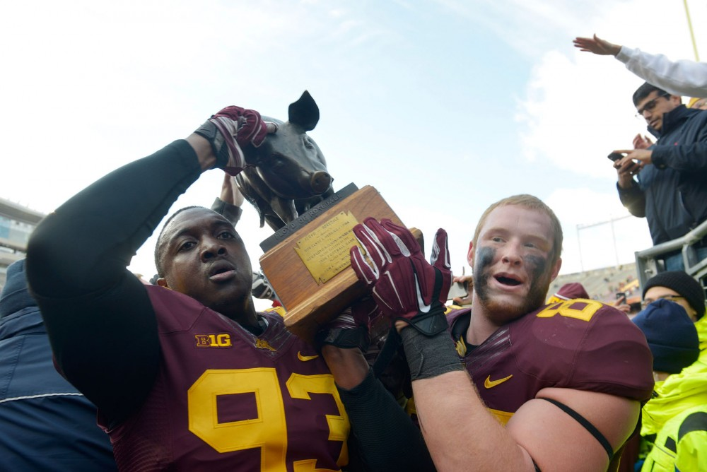 Minnesota tight end Maxx Williams, right, and defensive lineman Ben Perry, left, holds the pig after Minnesota beat Iowa 51-14 on Saturday at TCF Bank Stadium.