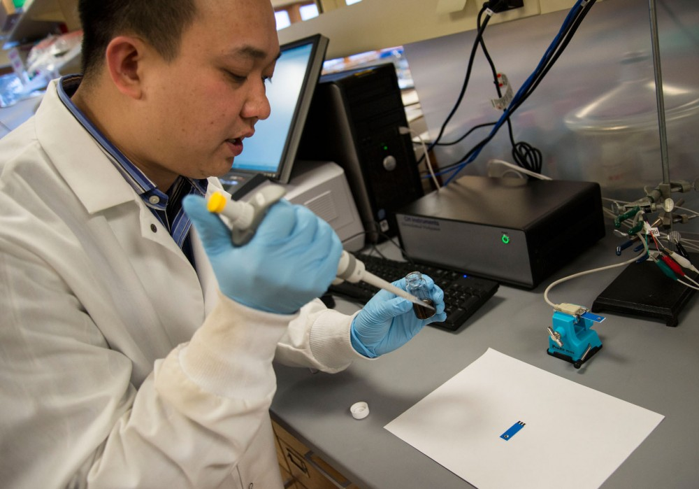 Post doctoral research associate Minphuong Bui demonstrates how the sensor within the handheld device will detect nitrate in soil Friday at Kaufert Laboratory in St. Paul.