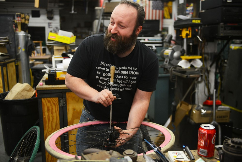 Eric Noren, owner of Peacock Groove, works on a customer's bike Sunday afternoon in Minneapolis. His Voltron bike will be featured in the Design Cycles show at the Goldstein Museum, which is opening Friday.