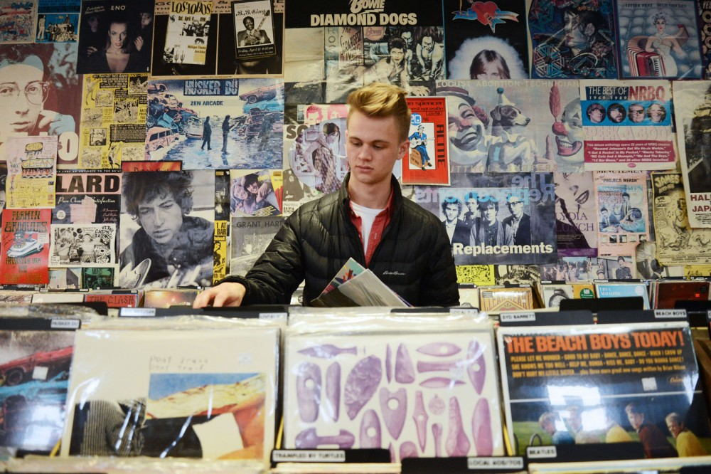 Global studies and history major Tyler Boesch looks at vinyl records at Treehouse Records in Minneapolis on Monday. Boesch began buying vinyls after his mom gave him a record player last Christmas.