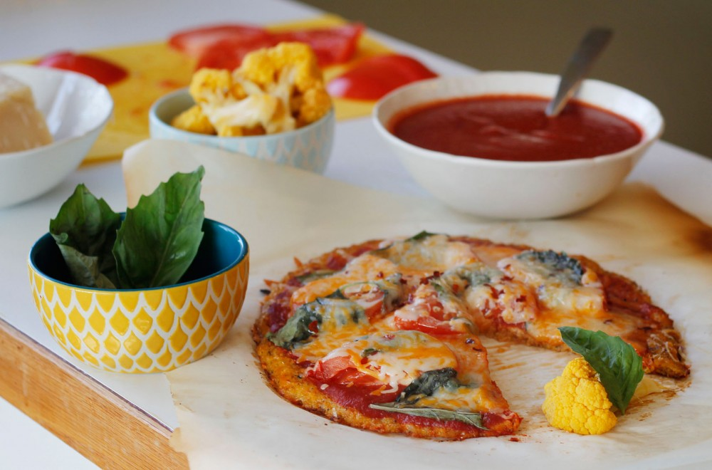 A fresh tomato and basil topped pizza, made with a cauliflower pizza dough crust.