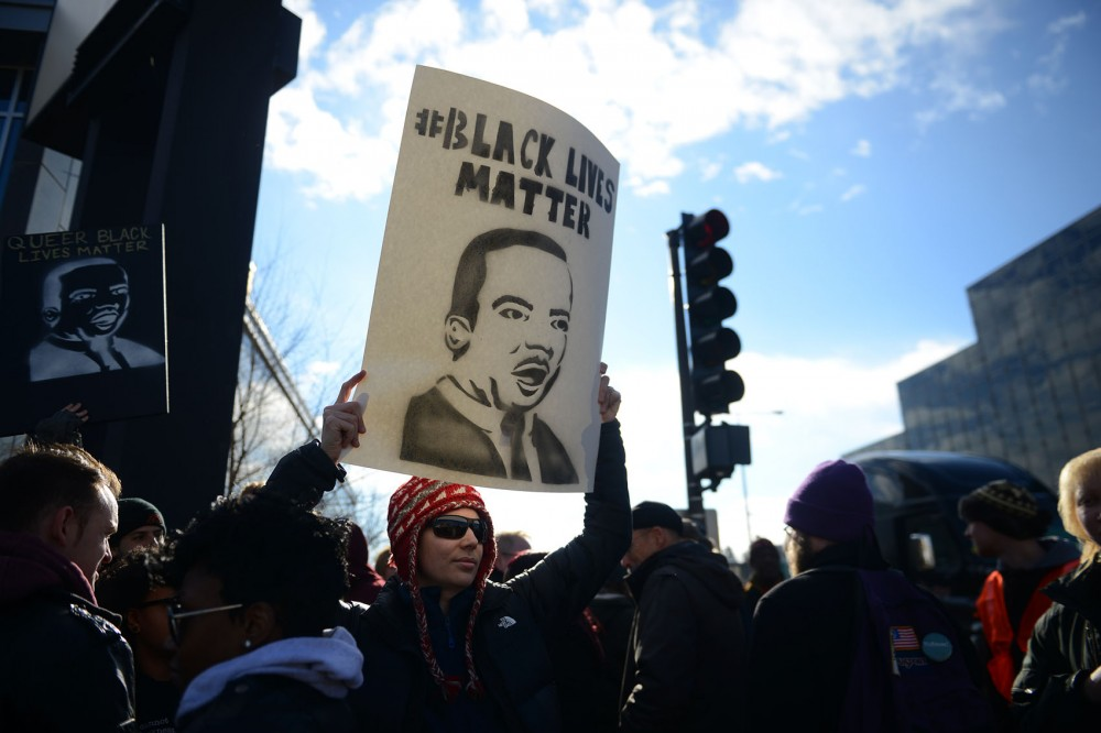 Demonstrator Cathy Stone holds up a sign at the beginning of Monday's march in St. Paul.