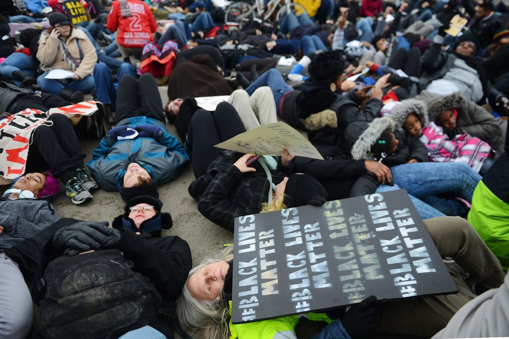 Demonstrators lay on the ground while participating in a