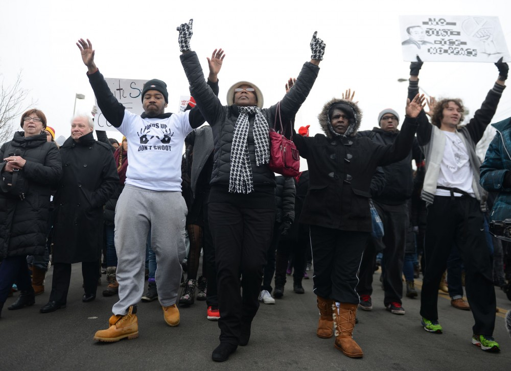 Demonstrators march with their hands raised during Monday's march in St. Paul.